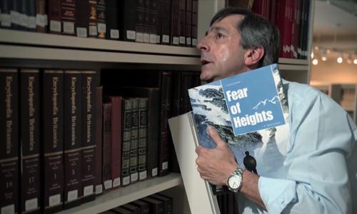 Người đàn ông vất vả khi tìm sách ở thư viện