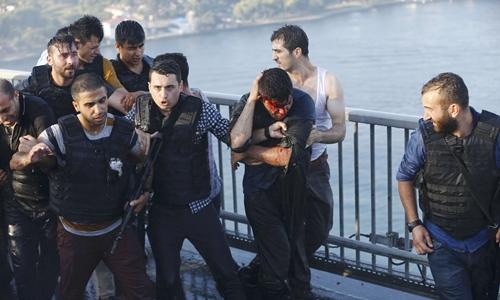 Cảnh sát bảo vệ một binh sĩ tham gia đảo chính đã đầu hàng trên cầu Bosphorus, thành phố Istanbul, ngày 16/7. Ảnh: Reuters.
