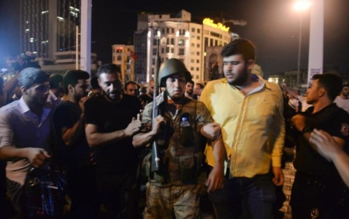 A Turkish soldier, arrested by civilians, is walked to be handed to police officers, in Istanbuls Taksim square, early Saturday, CREDIT: AP