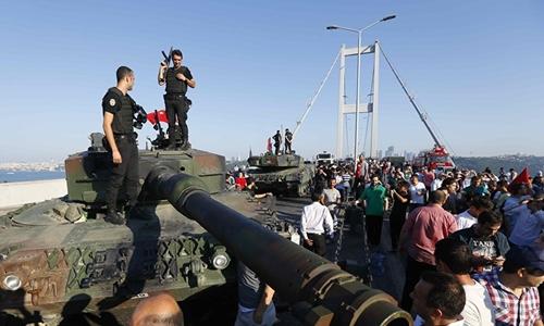 Cảnh sát vũ trang Thổ Nhĩ Kỳ đứng trên chiếc xe tăng phe đảo chính bỏ lại tại cầu Bosphorus, Istanbul. Ảnh: Reuters.