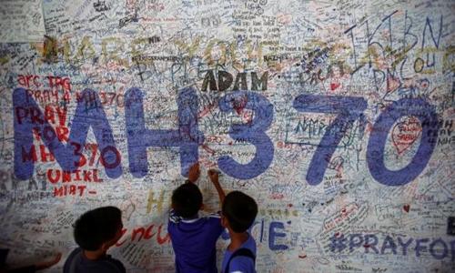 Bên ngoài sân bay quốc tế Kuala Lumpur, trẻ em viết những dòng cầu mong điều may mắn đến với các hành khách trên chuyến bay MH370 mất tích. Ảnh: Reuters.