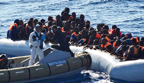[Caption]Migrants sit in their rubber boat during a rescue operation by Italian navy ship Borsini (unseen) off the coast of Sicily, Italy, in this handout picture courtesy of the Italian Marina Militare released July 19, 2016.