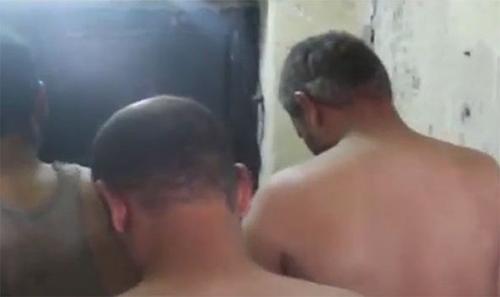 3 tên bị ép phải tháo mạng che mặt và cởi đồ trước mặt lực lượng quân đội để nhận dạng và kiểm tra vũ khí.