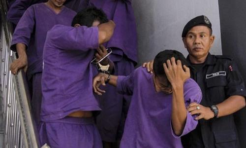 Cảnh sát dẫn giải các nghi phạm hiếp dâm tới một phiên tòa ở Malaysia. Ảnh: Independent.