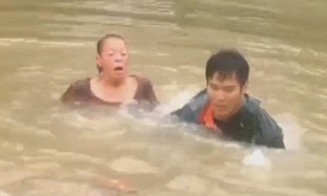 Người hùng nhảy xuống nước lũ cứu người và chó kẹt trong ôtô
