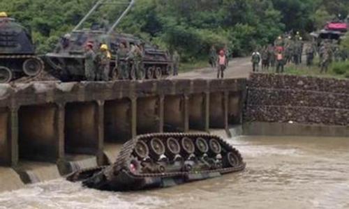 Xe tăng Đài Loan lật nhào xuống suối, nguyên nhân ban đầu được cho là kẹt xích. Ảnh: CNA.