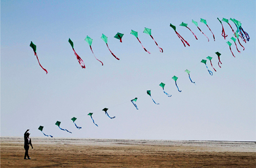 [Caption]An Indian participant flies a train of kites at the International Kite Festival at white sand in the Rann of Kutch, a seasonal salt marsh located in the Thar Desert, in Dhordo, about 500 kilometers (311 miles) from Ahmadabad, India. (AP Photo/Ajit Solanki)