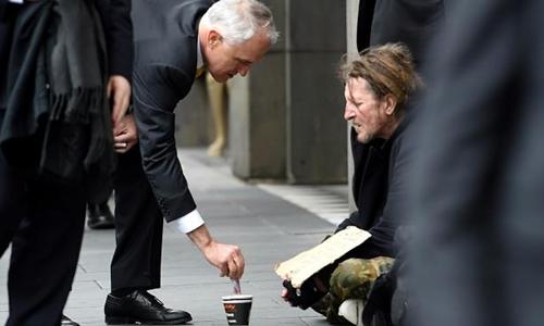 Thủ tướng Australia Malcolm Turnbull cho tiền một người ăn xin ở thành phố Melbourne. Ảnh: AAP.
