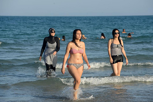 [Caption]Tunisian women, one (L) wearing a burkini, a full-body swimsuit designed for Muslim women. / AFP / FETHI BELAID (Photo credit should read FETHI BELAID/AFP/Getty Images)