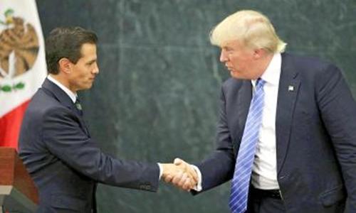 Tỷ phú Donald Trump bắt tay Tổng thống Enrique Pena Nieto trong chuyến thăm Mexico hôm 31/8. Ảnh: AP