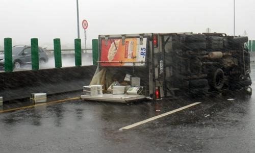 Sức gió của hoàn lưu bão Meranti làm lật xe tải chở hàng ở Đài Loan. Ảnh: CNA.