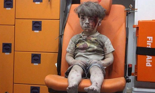 Cậu béOmran Daqneesh ngồi đờ đẫn trên xe cứu thương sau khi được giải cứu từ một ngôi nhà sập ở Aleppo, Syria. Ảnh:AMC