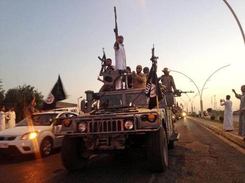 Phiến quân Nhà nước Hồi giáo diễu hành trên xe quân sự cướp được từ lực lượng an ninh Iraq ở thành phố Mosul hồi tháng 6. Ảnh: AP.