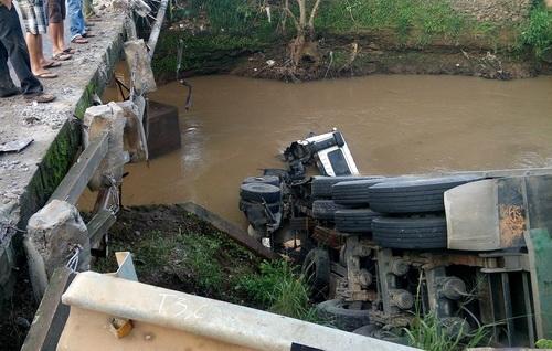 Xe đầu kéo nằm tông sập lan can cầu rớt xuống suối. Ảnh: Thái Hà