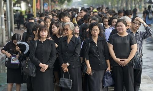 Lần đầu tiên trong 70 năm qua, người Thái thức dậy khi vị vua của họ không còn trên cõi đời, nhiều người chọn mặc đồ đen bày tỏ đau buồn. Ảnh: AP.