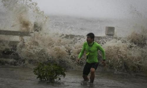 Một người đàn ông Trung Quốc mạo hiểm chơi đùa với những con sóng biển khi bão Sakira vào đảo Hải Nam. Ảnh: Reuters.
