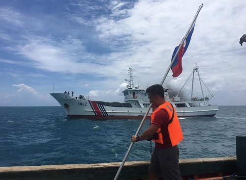A Filipino activist holds a national flag while a Chinese coastguard ship sails close by at Scarborough Shoal, just 230 kilometres (143 miles) off the main Philippine island of Luzon, in the South China Sea in June 2016 (AFP Photo/)