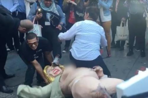 Người phụ nữ cố ngồi lên bức tượng nhằm ngăn người khác dựng nó lên. Ảnh: Metro