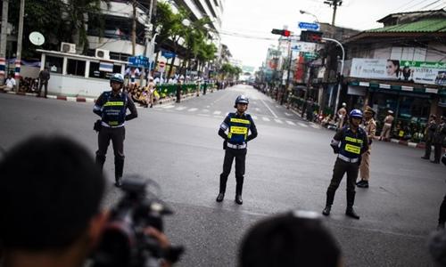 Cảnh sát Thái Lan đứng bảo vệ các con đường nơi có xe chở linh cữu nhà vua Bhumibol Adulyadej đi qua. Ảnh: CNN.