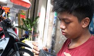 Chàng trai bị bướu máu sửa giầy miễn phí ở Sài Gòn
