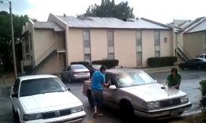 Hai phụ nữ rửa ôtô dưới mưa