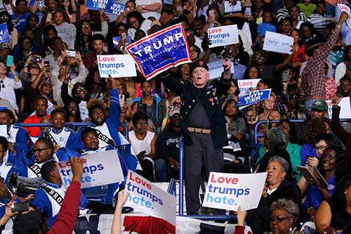 Người đàn ông đứng lên và giơtấm biểu ngữ ủng hộ ông Trump làm những người xung quanh la ó phản đối.