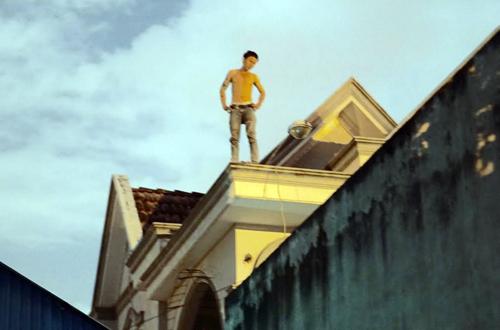 Nam thanh niên ngáo đá cố thủ trên nóc nhà 2 tầng suốt 7 giờ. Ảnh: Nguyệt Triều
