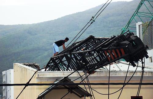 Cần cẩu đè lên mái nhà bên cạnh. Ảnh: Quy Nhơn