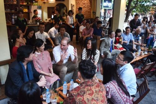 Hoàng tử William trò chuyện với ca sĩ Hồng Nhung, nhạc sĩ Thanh Bùi và diễn viên Xuân Bắc (các đại sứ của chiến dịch bảo vệ động vật hoang dã tại VN) cùng các khách mời tại một quán cà phê ở phố Thuốc Bắc. Ảnh: Giang Huy
