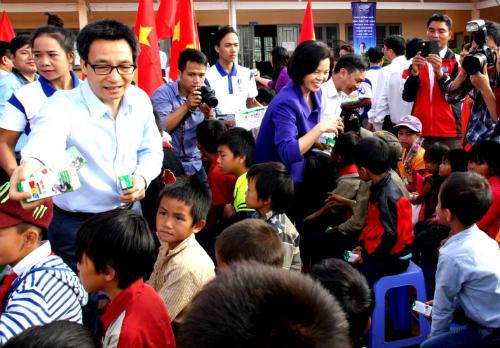 Phó Thủ tướng Vũ Đức Đam và bà Bùi Thị Hương  Giám Đốc Điều hành Vinamilk đang trao sữa học đường của Vinamilk cho học sinh trường tiểu học dân tộc khó khăn nhất của tỉnh Đắk Nông.Ảnh: Kh.Uyên