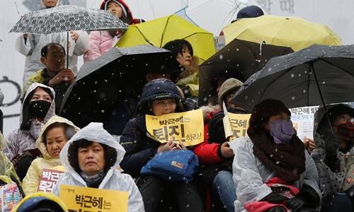 Người dân Hàn Quốc đội mưa tuyết biểu tình đòi Tổng thống Park Geun-hye từ chức tại Seoul ngày 26/11. Ảnh: Reuters.