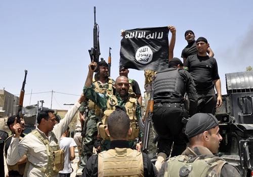 Lực lượng an ninh Iraq gỡ bỏ một lá cờ Nhà nước Hồi giáo tại thị trấn Hit, tỉnh Anbar, hồi tháng 4. Ảnh: Reuters.