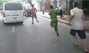 Công an chạy bộ đuổi theo xe biển xanh trên phố