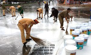 Cảnh sát giao thông dầm mưa quét dọn sơn đổ trên đường