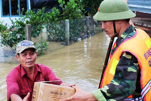 2Giữa dòng nước lũ ông Trung tá túc nhà hàng xóm, lũ rút ông mới trở về nhà nhận hàng cứu trợ.