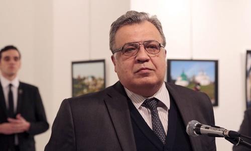 Đại sứ Nga Andrei Karlov trước lúc bị ám sát, tay súng mặc áo đen đứng sau lưng ông. Ảnh: AP.