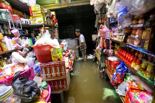 6. Tương tự, tiệm tạp hóa tại chợ Ngã Tư Ga của anh Nguyễn Văn Chuyên cũng ngập sâu quá đầu gối. Đến 12h đêm mà tôi vẫn chưa dọn xong hàng. Tại nhà tôi chưa nâng nền nên nước khó thoát, anh Chuyên cho biết.