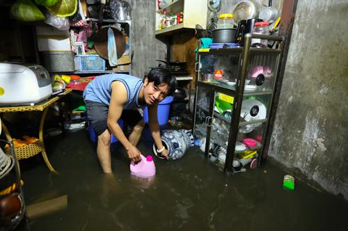 7. Lúc 11h đêm, anh Nguyễn Hồng Vinh (36 tuổi, phường Thạnh Lộc) vẫn cố gắng thu dọn nhà cửa, chờ nước rút.