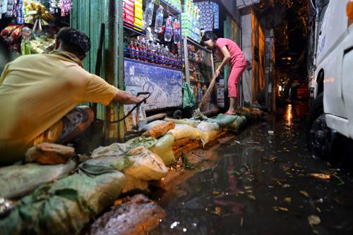 9. Hai vợ chồng nhà anh Long phải ngưng bán hàng để đắp bao ngăn nước tràn vào và thu dọn rác trôi dạt về.