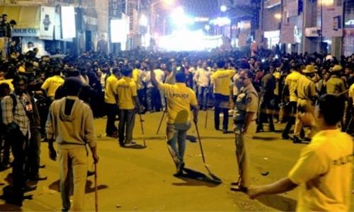 Đám đông tụ tập ăn mừng giao thừa và cảnh sát Ấn Độ. Ảnh: AFP