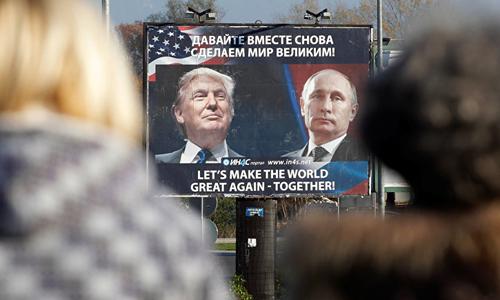 Hai người đi bộ nhìn tấm áp phích có chân dung ông Putin và ông Trump với khẩu hiệu Hãy cùng khiến thế giới vĩ đại trở lại tạiDanilovgrad, Montenegro, đông nam châu Âu. Ảnh: Sputnik