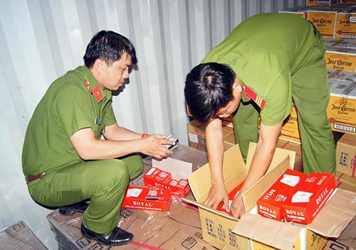 Cảnh sát kiểm tra lô hàng do giám đốc buôn lậu. Ảnh: Nguyệt Triều