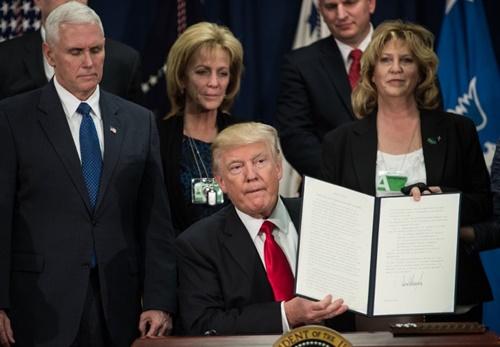 Tổng thống Donald Trump ký sắc lệnh bắt đầu xây tường tại biên giới với Mexico tại Bộ An ninh Nội địa ngày 25/1. Ảnh: AFP.
