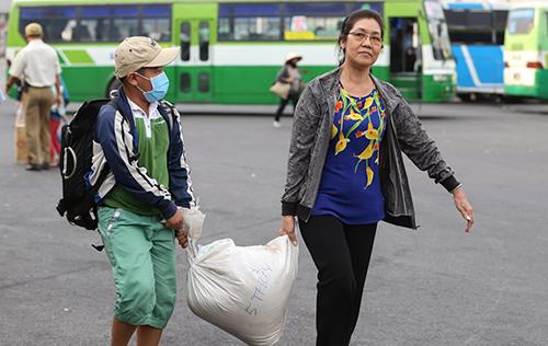 4. Người dân tay xách nách mang quà cáp, hành lý khi trở lại thành phố.