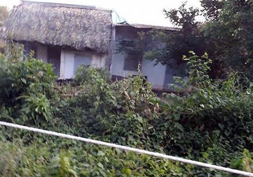 Bao tải đựng thi thể nạn nhân nằm gần ngôi nhà hoang. Ảnh: V.M
