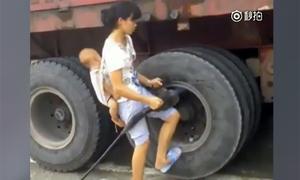 Người mẹ địu con tháo lốp xe tải