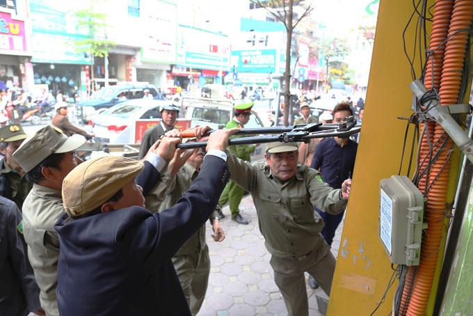 Cán bộ phường mang kìm, búa tạ để dọn vỉa hè Hà Nội