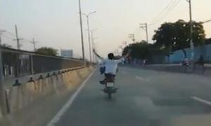 Quái xế lái xe máy bằng chân trên quốc lộ 1