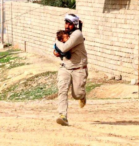 Chiến binh PMU ôm em bé trước khi trúng đạn bắn tỉa của IS. Ảnh:Almasdar news.