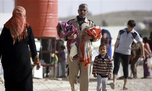 Một người tị nạn Iraq tháo chạy khỏi Mosul bế con tại một trại14 kilometers from the Iraqi border in Syrias northeastern province of Hasakah, on March 13, 2017. (Photo by AFP)